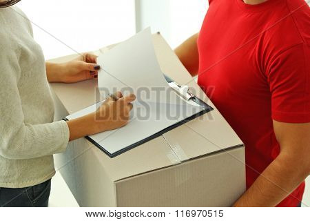 Woman signing receipt of delivery package, close up