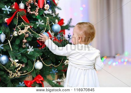 Funny baby girl decorating Christmas tree on bright background