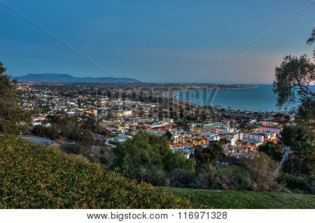 Overlooking town nestled against ocean shore.