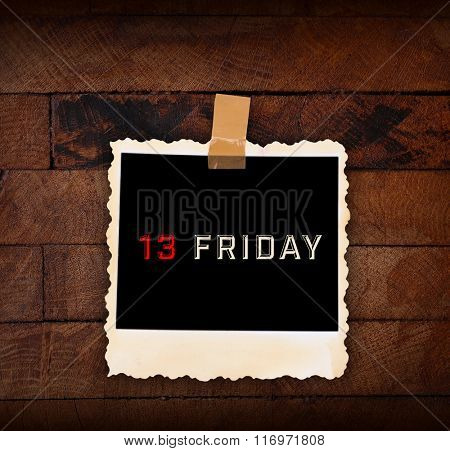 Photo paper with text Friday 13 on wooden background