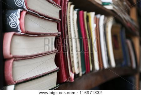Many books on bookshelf in library, image with perspective distortion