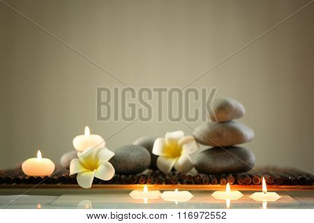 Spa still life with stones, candles and flowers in water on blurred background