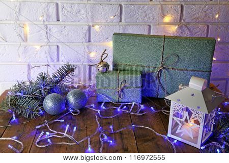 Wrapped gifts for Christmas with lantern and garland on brick wall background