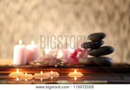 Spa still life with stones, candles and flowers in water on light blurred background