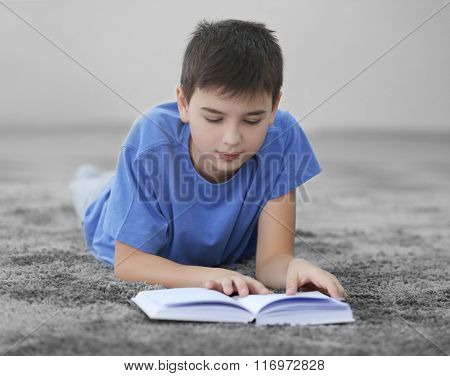 Little boy reading book on a floor at home
