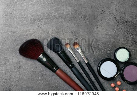 Makeup brushes and cosmetics on gray background