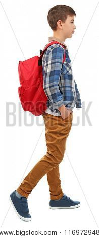 Cute little boy with red backpack going right, isolated on white