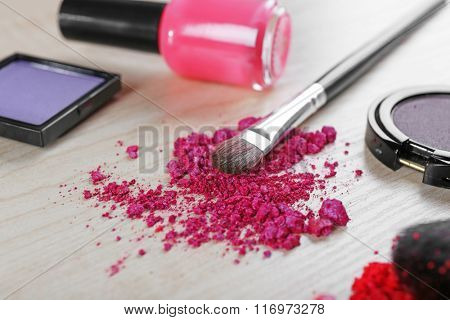Makeup brush and cosmetics on a wooden background