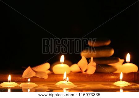 Spa still life with candles in water on dark background