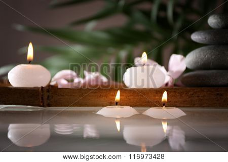 Spa still life with candles in water on natural blurred background