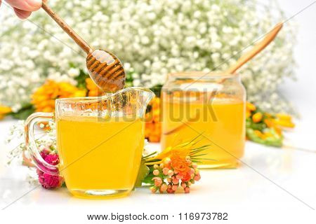 golden honey and colorful flowers, studio shot