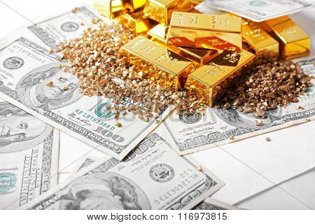 Gold bars and nuggets on dollar banknotes, close up
