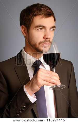 Man sniffing red wine in glass on blue background
