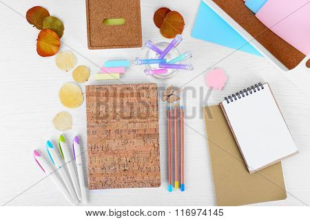 Set of coloured pens, pencils, stickers with notebook on white table