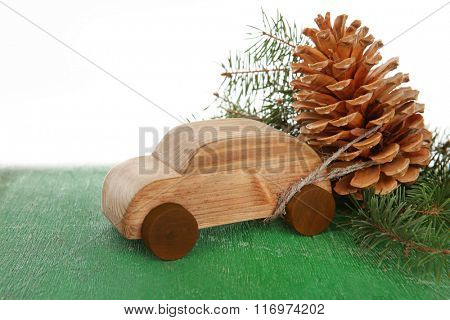 Wooden toy car with pine cone and sprigs on a table over white background