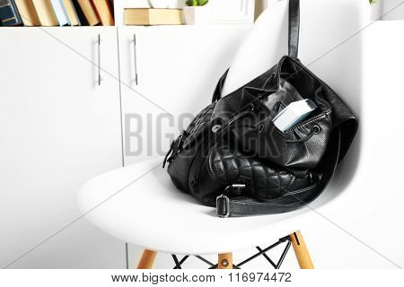 Fashion female backpack with book on white chair