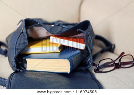 Fashion female backpack with books and glasses on a sofa, close up
