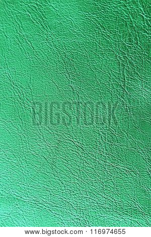 Green leather texture with crumpled uneven surface