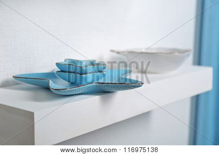New blue dish on a shelf closeup