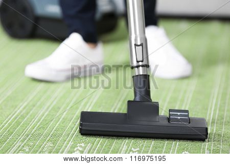 Cleaning concept - woman cleaning the room with carpet sweeper, close up