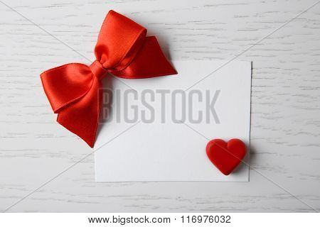 Blank present card with ribbon bow and small heart on wooden background