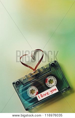Retro audio cassette with tape in shape of heart on green blurred background