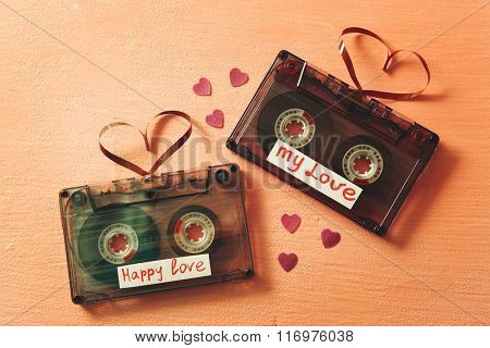 Retro audio cassettes with tapes in shape of hearts on pink textured background