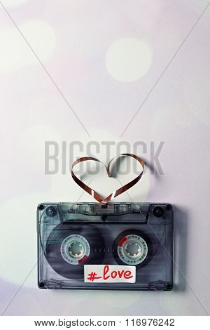 Audio cassette with magnetic tape in shape of hearts on light background