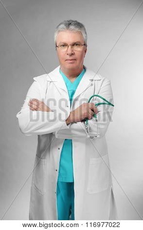 A handsome doctor with crossed arms, on grey background