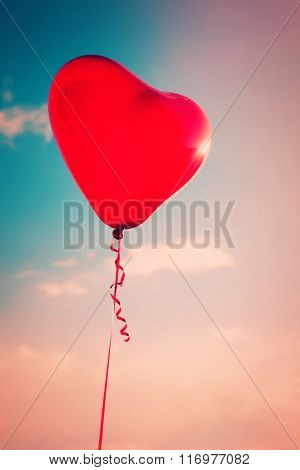 beautiful red heart shape balloon against sky with clouds