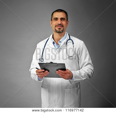 Portrait of a doctor with prescription board in hands  on grey background