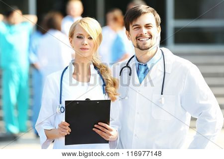 Medical concept - two doctors with stethoscopes and prescription clipboard