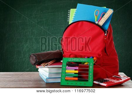 Red bag with school equipment on wooden table near blackboard