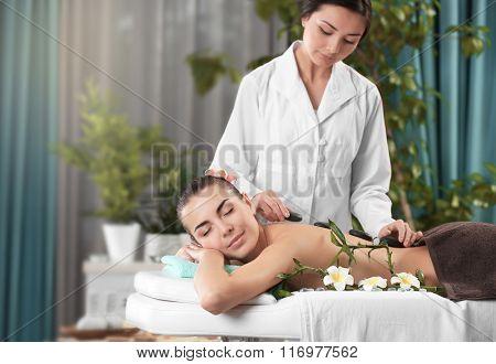 Woman getting a hot stone massage at spa salon