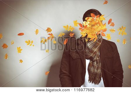 Young man and falling autumn leaves on gray background