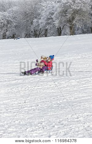 Two Girls Sledding On A Mountainside.