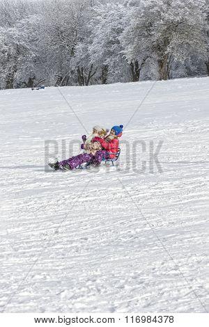 Two Girls Sledding On A Mountainside.