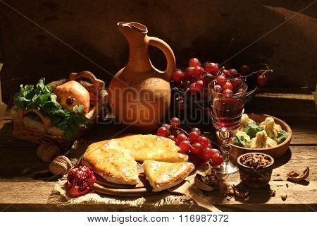 Still-life With A Pie With Cheese, Red Wine, Nuts And Fruit