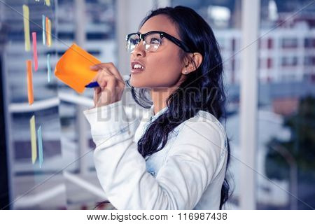 Asian woman removing sticky note by glass wall