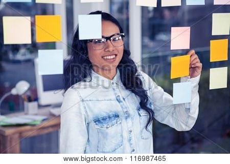 Asian woman writing on sticky notes on glass wall