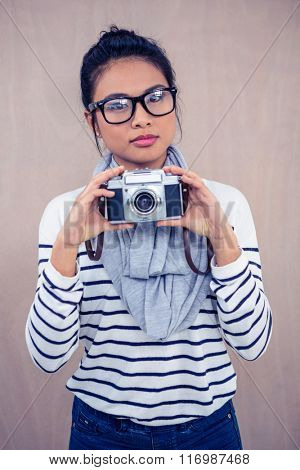 Attractive Asian woman holding camera and looking at the camera
