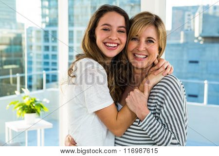 Happy mother and daughter hugging each other at home