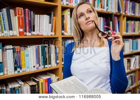 Thoughtful female student holding a book at the university