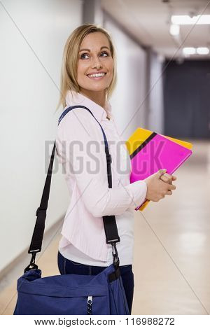 Happy female student walking in the hallway at the university