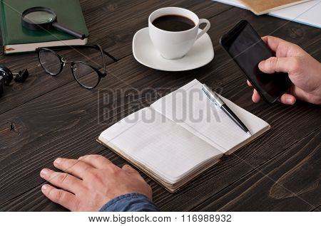 Man Working Using A Smartphone On The Office Desktop