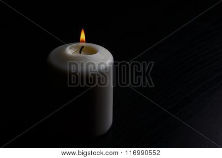 White Lit Candle On The Black Wooden Table