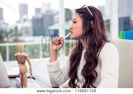Focused Asian woman with pen on chin in office