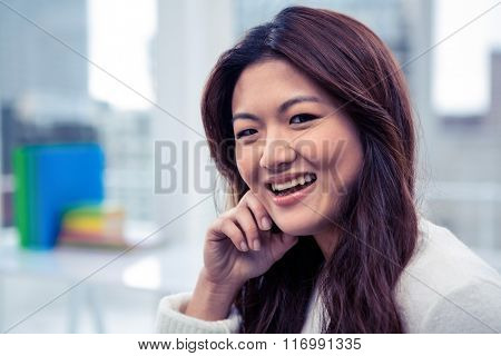 Smiling Asian woman with hand on cheek posing for camera