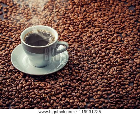 Hot aromatic coffee drink in the white cup with saucer and spoon with beans background