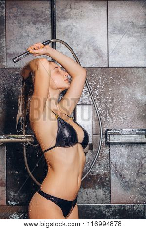 autiful woman standing at the shower. In a black bathing suit